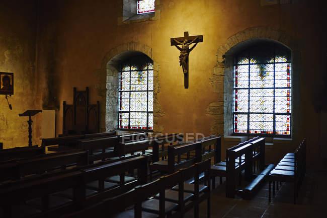 Kirche, Innenraum mit Bänken und beleuchteten Kreuz — Stockfoto