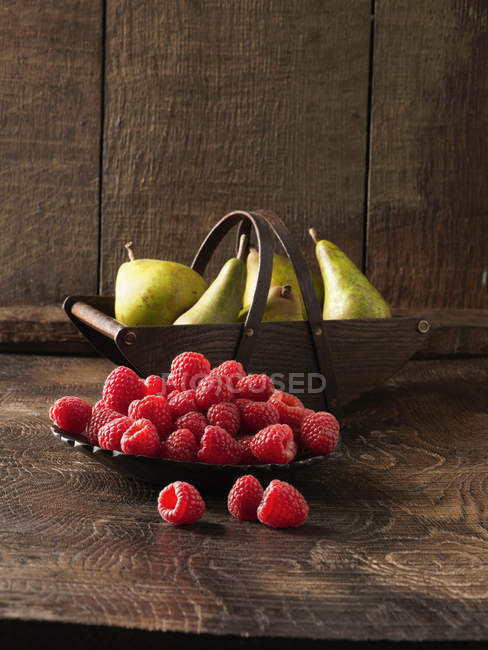 Bowl of raspberries and pears — Stock Photo
