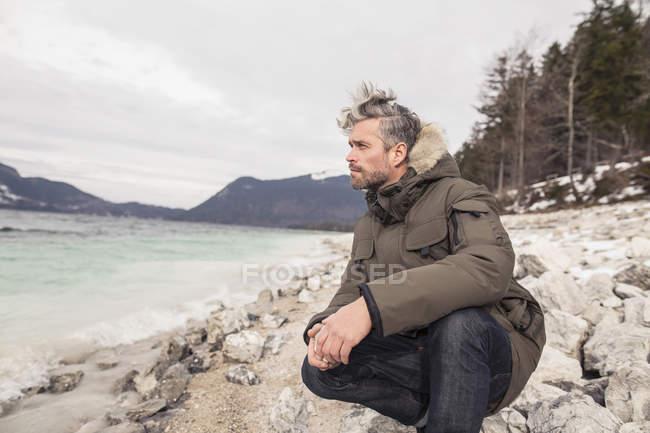 Homem adulto médio agachado ao lado do lago, Alpes Alemães, Alemanha — Fotografia de Stock