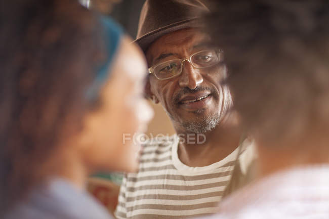 Over shoulder view of mature man chatting to couple, Ipanema beach, Rio De Janeiro, Brazil — Stock Photo