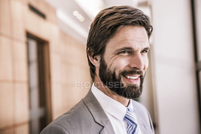 Bearded business man looking away smiling — Stock Photo