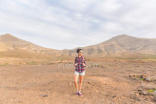 Молодая женщина, стоя в вулканический ландшафт, La Oliva, Фуэртевентура, Испания — стоковое фото