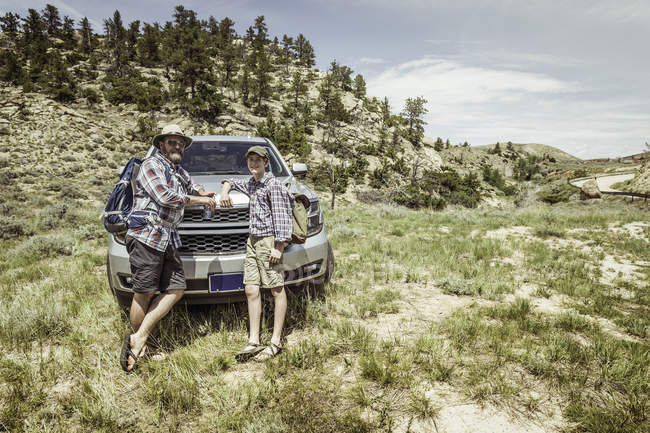 Portrait of man and teenage son on hiking road trip leaning on car hood in landscape, Bridger, Montana, USA — Stock Photo