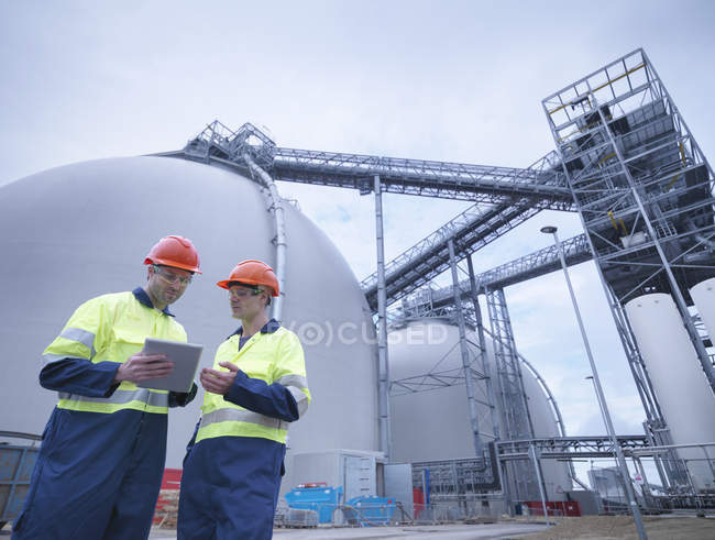 Workers using digital tablet at biomass facility — Stock Photo