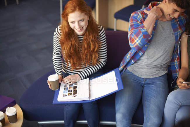 Jeune femme étudiante avec salle de café lecture de fichier en commun de plats à emporter — Photo de stock