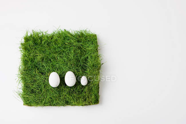 Три яйца на траве — стоковое фото