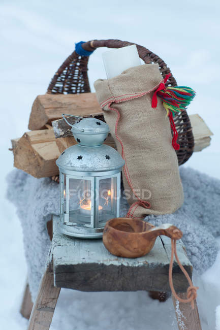 Basket with logs, candle lantern, wooden cup in snow — Stock Photo