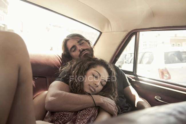 Joven pareja en viaje dormido en el asiento trasero de coche de época, ciudad del cabo, Sudáfrica - foto de stock