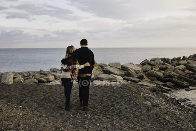 Pareja joven de pie junto al mar, vista trasera - foto de stock