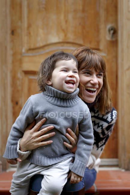 Madre e hija en la puerta, mirando hacia otro lado sonriendo - foto de stock