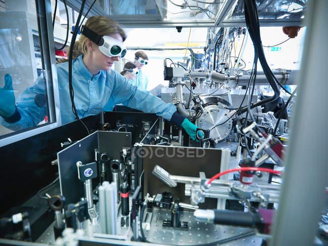 Cientista ajustando um espelho com uma mesa de óptica em primeiro plano e uma câmara de vácuo atrás — Fotografia de Stock