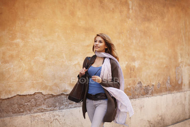 Elegant young woman strolling down street — Stock Photo