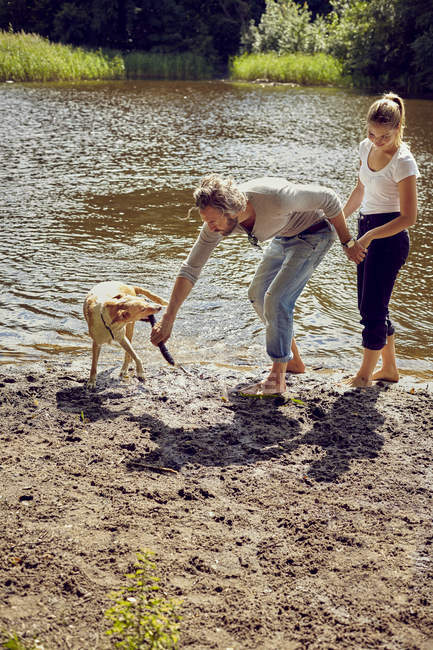 Couple playing with dog on riverside — Stock Photo