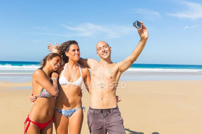 Homem e duas jovens mulheres vestindo roupa de banho tirando selfie na praia, El Cotillo, Fuerteventura, Espanha — Fotografia de Stock