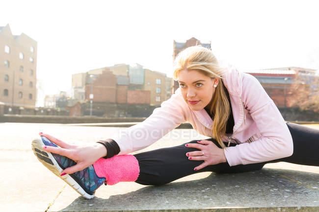 Молодая женщина упражнения и растяжки, на открытом воздухе — стоковое фото
