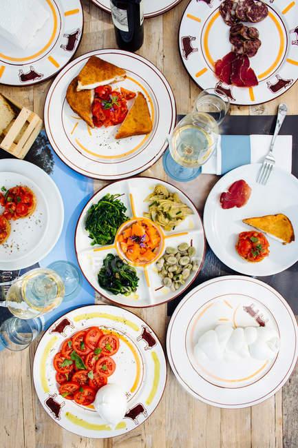 Вид сверху традиционной итальянской еды с мясное ассорти, сыр моцарелла и caprese салат — стоковое фото
