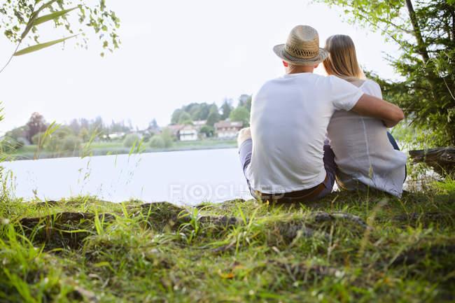 Вид сзади на пару, сидящую у озера — стоковое фото