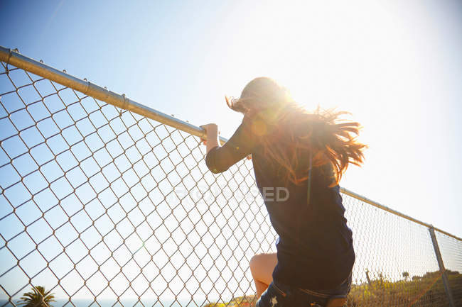 Young woman messing about on wire fence — Stock Photo