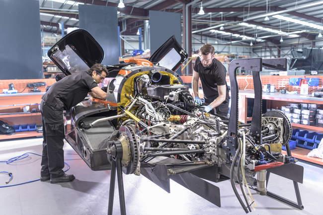 Ingegneri riparazione auto in auto da corsa fabbrica — Foto stock