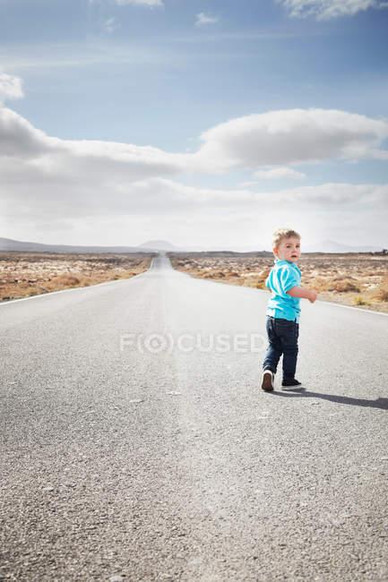 Niño caminando en camino rural pavimentado - foto de stock