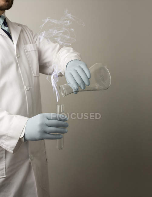 Scientist experimenting with liquid chemicals and test tube, cropped shot — Stock Photo