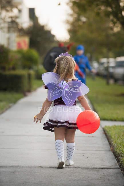 Vue arrière de la petite fille en costume va tour ou le traitement — Photo de stock