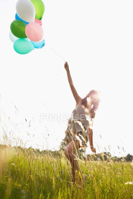 Mulher com balões de ar andando em campo — Fotografia de Stock