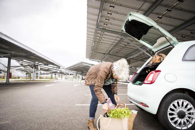 Зріла жінка в автостоянки, завантаження, покупок в завантаження автомобіля — стокове фото