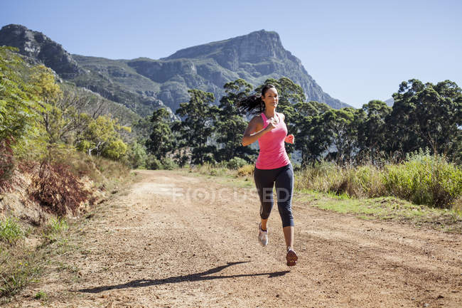 Young woman jogging in forest — Stock Photo