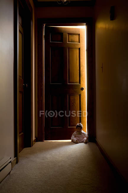 Doll in doorway in hallway — Stock Photo