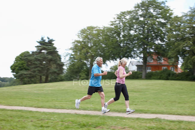 Couple plus âgé jogging ensemble à l'extérieur — Photo de stock