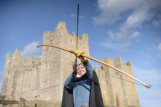 Studente di storia che impara il tiro con l'arco in abiti d'epoca fuori dal Castello di Bolton, edificio classificato di Grado 1 del XIV secolo, monumento antico pianificato — Foto stock