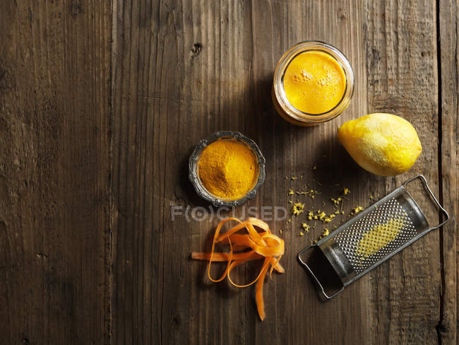 Top view of yellow raw juice with grated lemon and carrot on wood — Stock Photo