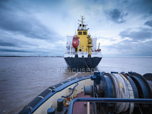 Tug towing ship out at sea — Stock Photo