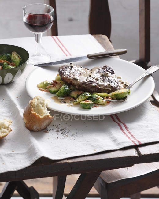 Steak with green pepper sauce, brussels sprouts and bacon — Stock Photo
