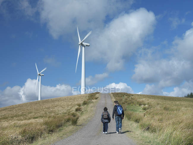 Two brothers walking on path at windfarm — Stock Photo