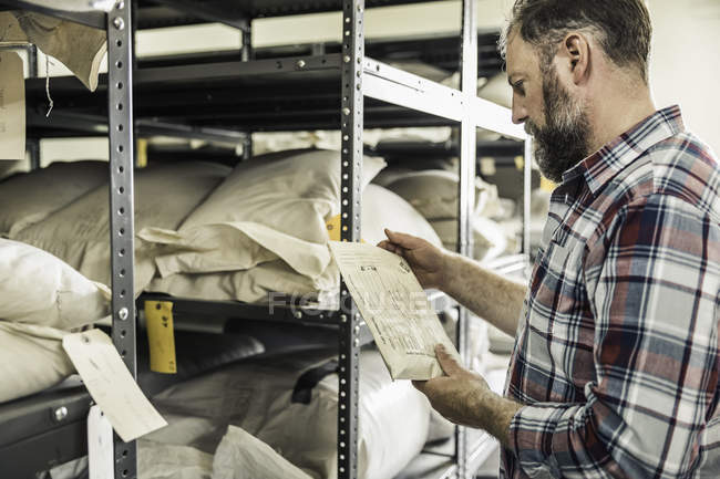 Scientist reading seed envelope in plant growth research centre warehouse — Stock Photo