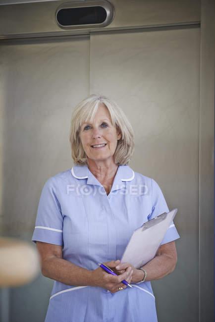 Retrato de enfermeira madura no corredor hospitalar — Fotografia de Stock