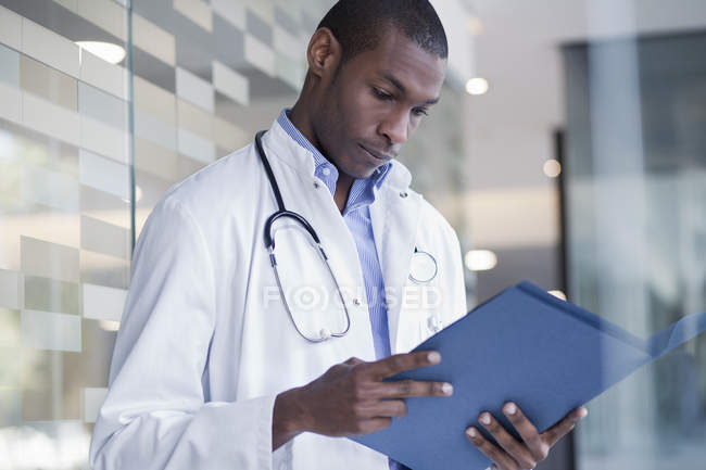 Doctor standing in hospital corridor and holding paperwork — Stock Photo