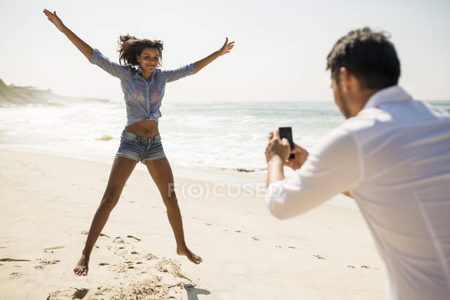 Mid adult man photographing girlfriend jumping, Arpoador beach, Rio De Janeiro, Brazil — Stock Photo