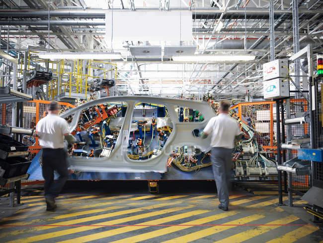 Розмиті працівників з автомобіля частина тіла в зварювання кондуктор у автомобільного заводу — стокове фото