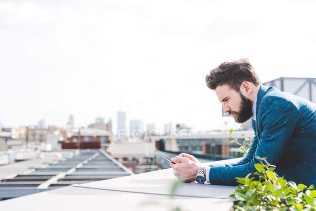 Joven hombre de negocios leyendo texto smartphone en la terraza de la azotea de la oficina - foto de stock