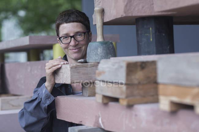 Stonemason quality checking blocks of stone, looking at camera smiling — Stock Photo