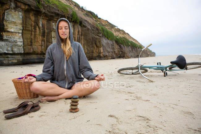 Mulher meditando com pedras na praia — Fotografia de Stock
