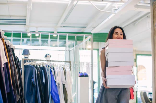 Donne nel negozio portando pila di scatole di scarpe — Foto stock