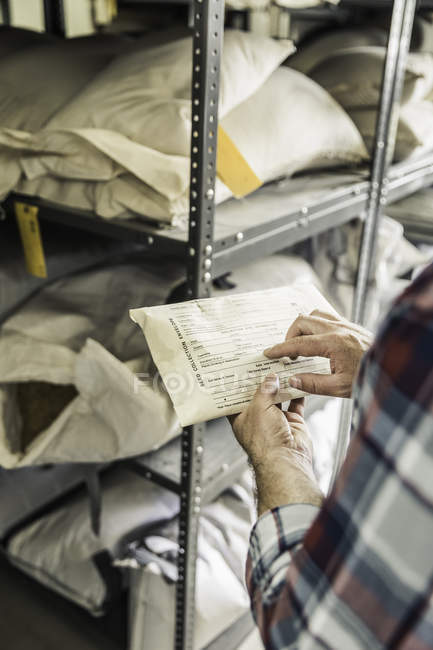 Hand of scientist pointing at seed envelope in plant growth research centre warehouse — Stock Photo