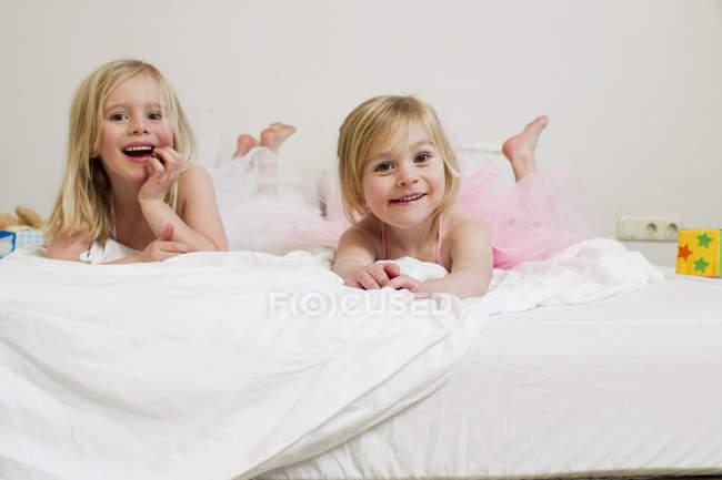 Портрет двух сестер дошкольника, лежащих на кровати — стоковое фото
