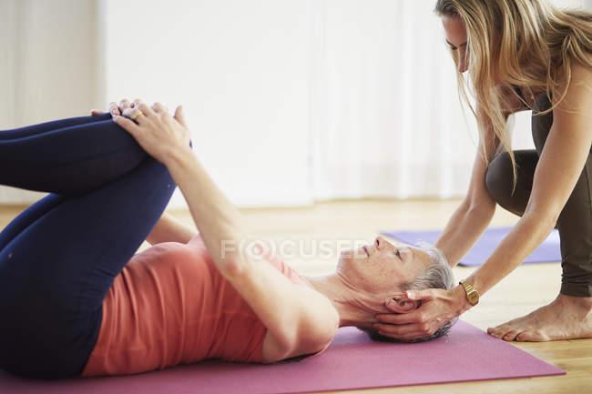 Зрілі жінки студент лежав на спині тримає коліна в пілатес клас — стокове фото