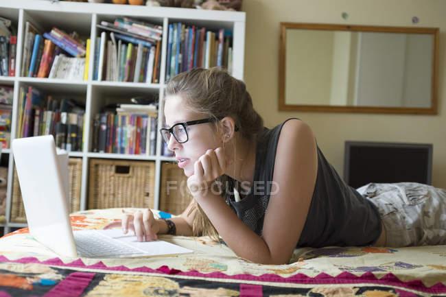Adolescente deitado na frente usando laptop — Fotografia de Stock