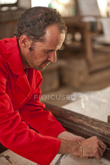 Плотник, работающий на деревянной раме — стоковое фото